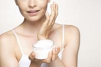 保湿クリームを顔に塗る若い外国人女性