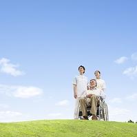 草原に立つ看護師と車椅子に乗る患者
