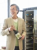 ワインのボトルを持つシニアの日本人男性