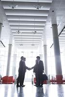 ホールで握手をするビジネスマン