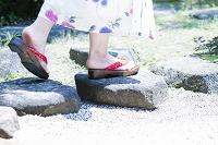飛石を歩く浴衣の女性