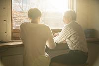 窓辺で談笑するシニアと若者