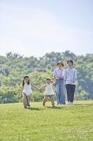 芝生の上を歩く日本人家族