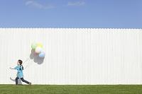 白い塀の前でカラフルな風船を持つ女の子