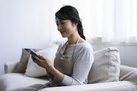 スマートフォンを見るエプロンを着けた40代日本人女性