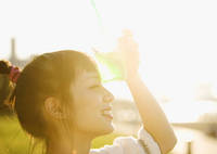 眩しい日差しを遮る若い日本人女性