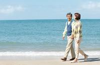 海岸を歩く中高年夫婦