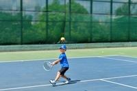 テニスレッスンを受けている男の子