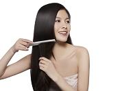 髪を梳かす黒髪の女性
