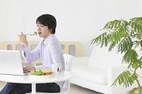 朝食を食べながらホームオフィスで仕事をする若い男性