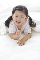 ベッドの上で布団をかぶり笑顔の女の子