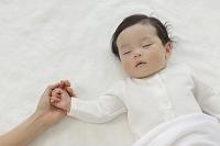 眠る赤ちゃんとお母さんの手