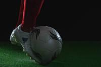 水しぶきとサッカーボールを蹴る足元