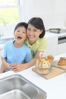 明るいキッチンに立つお母さんと子供