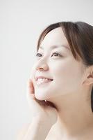 顔に手をあてる笑顔の日本人女性