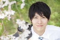 桜の下で微笑むビジネスマン