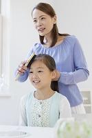 母に髪を結んでもらう女の子