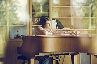 ピアノの前に座る女性
