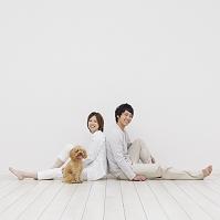床に座るカップルとトイプードル 犬