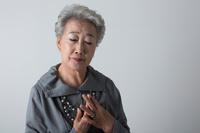 胸元に両手をあてる日本人のシニア女性
