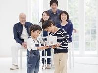 住宅模型を持った男の子と3世代家族