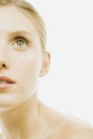 顔に保湿クリームをつけた女性