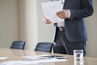 会議室で書類を持って立つビジネスマン