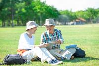 芝生に座る日本人シニア夫婦