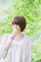新緑とソフトクリームを食べる女性