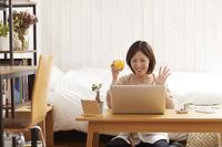 パソコンでオンライン飲み会を楽しむ日本人女性