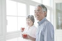ジュースを持つ笑顔のシニア夫婦