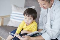 息子に絵本の読み聞かせをする父親