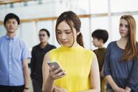駅でスマホを見る日本人女性