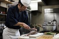 鯛をさばく調理師