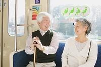 電車に乗っているシニア夫婦