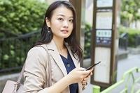 停留所でバスを待つ日本人女性
