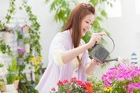 花に水遣りする笑顔の日本人女性