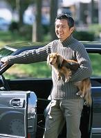 車と熟年男性と犬