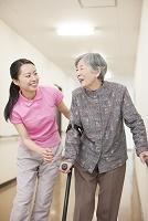杖をついて歩行訓練するおばあちゃんと介護士の女性