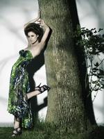 木に寄りかかるドレスアップした女性