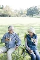 公園でピクニックをするシニア夫婦