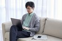 ソファでノートパソコンを操作する日本人男性