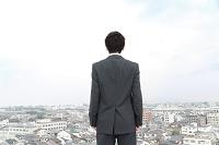 街並みを背に佇む後姿のビジネスマン