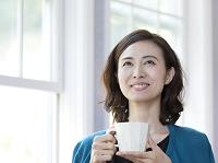 コーヒーカップを持つ40代の日本人女性