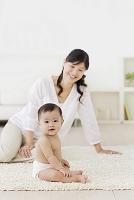 リビングでくつろぐお母さんと裸の赤ちゃん