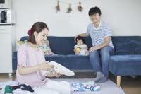 洗濯物をたたむ母親