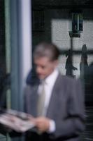 路上で新聞を読むビジネスマン