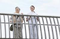 橋の上から遠くを見つめるシニア女性と女性介護士