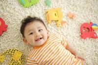 カーペットの上で寝転ぶ赤ちゃんと, カラフルなおもちゃ