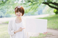新緑とホワイトボードを持つ日本人女性